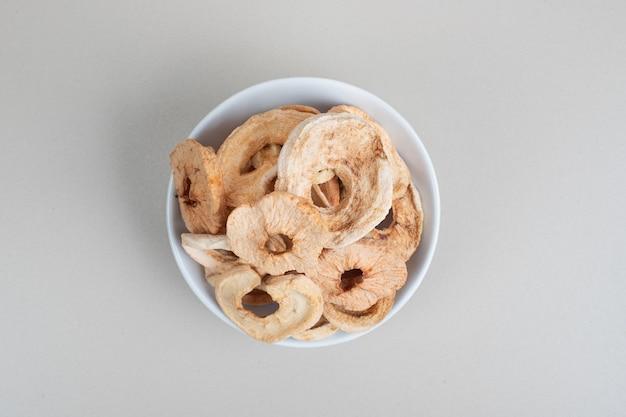 흰색 표면에 말린 된 사과 링의 그릇