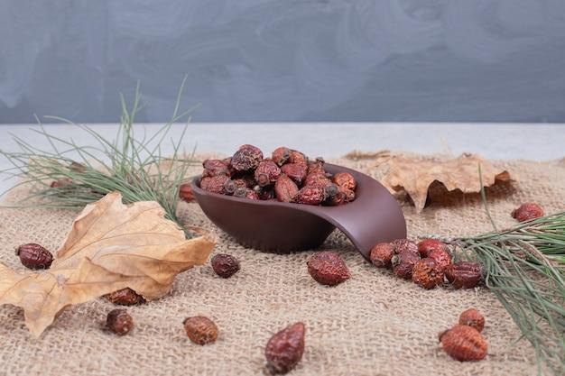Чаша сушеной клюквы и листьев на мешковине. фото высокого качества