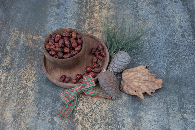 大理石の背景に乾燥したローズヒップ、リボン、松ぼっくりのボウル。高品質の写真