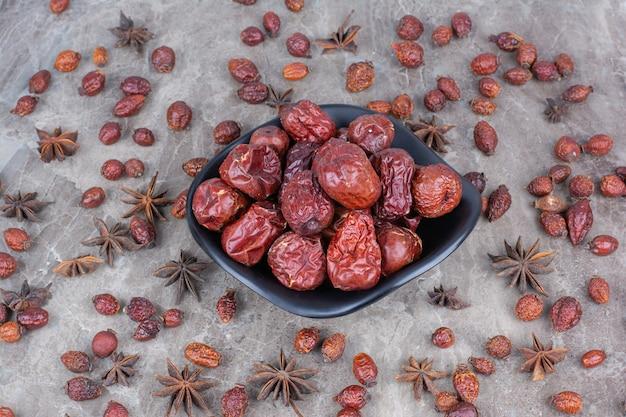 Чаша сушеных плодов шиповника на каменном фоне.