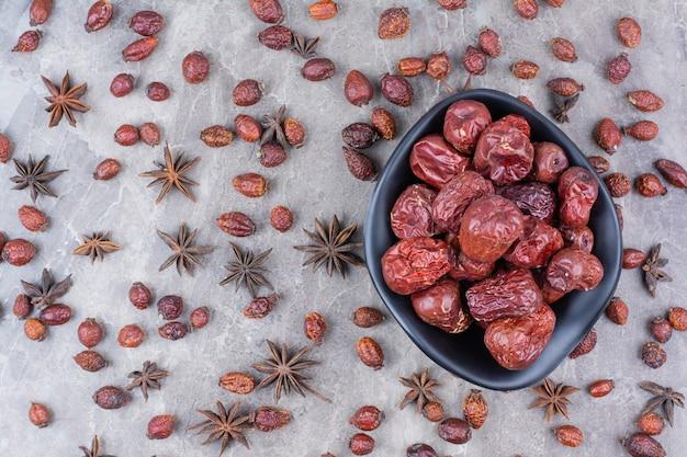Чаша сушеных плодов шиповника на каменном столе.