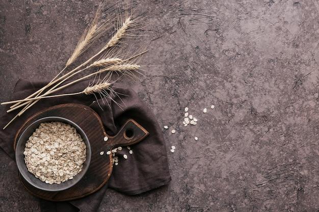 Чаша сухих овсяных хлопьев с колосьями пшеницы на темной поверхности. приготовление овсяной каши. вид сверху со свободным пространством для копирования