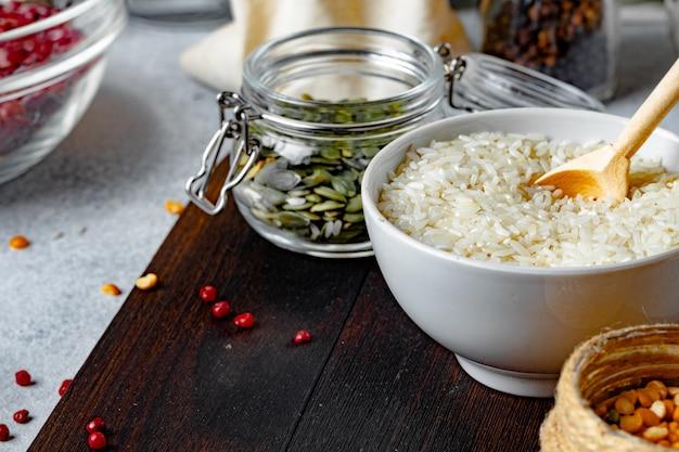 Чаша из сухого риса и стеклянная банка с тыквенными семечками на деревянный стол