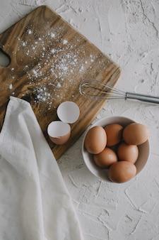 白い表面のまな板の横にある卵のボウルと銀の泡立て器