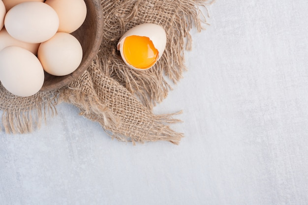 Миска с яйцами рядом с желтком в скорлупе на куске ткани на мраморном столе.