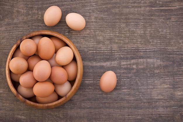 나무 배경에 계란 그릇