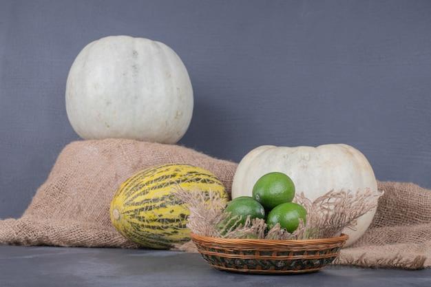 Feijoas, 흰색 호박과 파란색 벽에 멜론의 그릇.