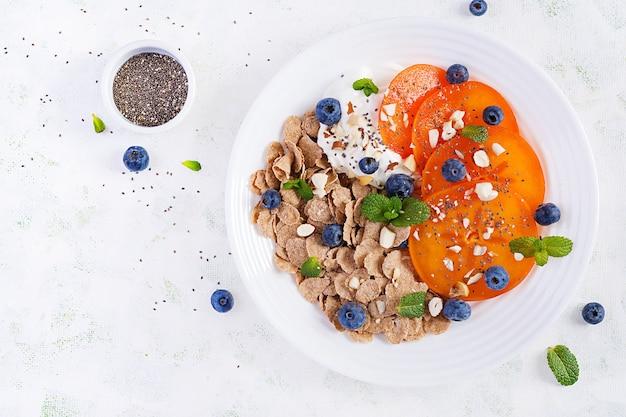 Чаша хлопьев с йогуртом, черникой и хурмой на белом деревянном столе. фитнес-питание. накладные, вид сверху, плоская планировка