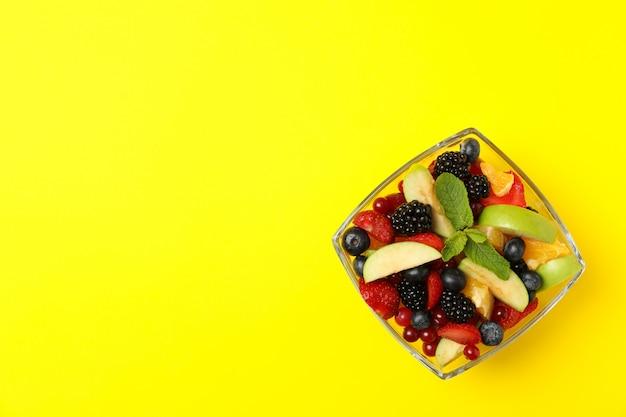 Чаша салата из свежих фруктов на желтом