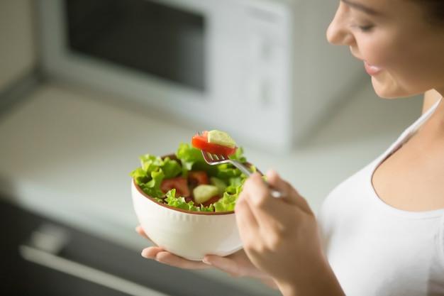 新鮮な緑のサラダのボウルは、女性の手で保持