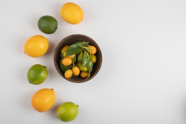 Чаша свежих кумкватов, лаймов и лимонов на белом столе.