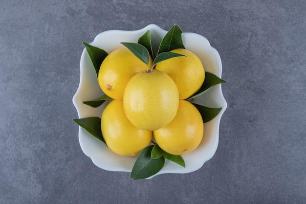 Миска свежих лимонов на сером фоне.