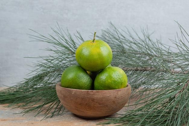 枝のある大理石のテーブルに新鮮なみかんのボウル。