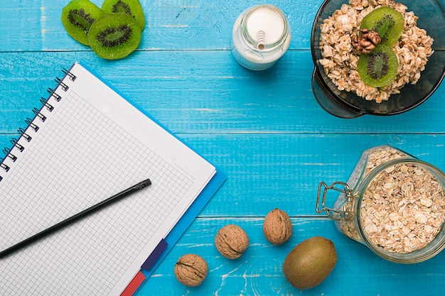 ティールの素朴なテーブルにキウイとナッツを添えた新鮮なオートミールのお粥のボウル、朝食用の温かく健康的な料理。上面図。コピースペース