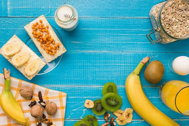 ティールの素朴なテーブルにキウイとナッツと新鮮なオートミールのお粥のボウル