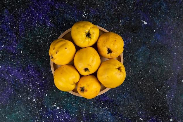 暗いテーブルに置かれた新鮮なマルメロの果実のボウル。