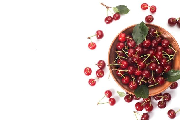 Чаша из свежей красной вишни на белом фоне