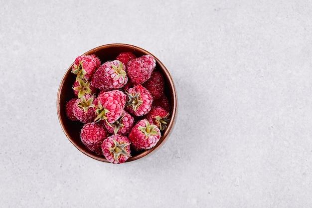 흰색 바탕에 신선한 빨간 나무 딸기의 그릇입니다.