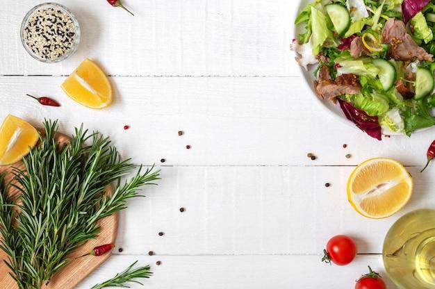 白い木製のテーブルに新鮮なサラダ、ローズマリー、レモン、スパイス、オイルのボウル。食品の背景。