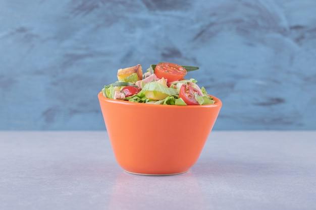 대리석 백그라운드에 소시지와 신선한 샐러드 그릇.