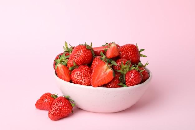 ピンクの表面に新鮮なイチゴのボウル