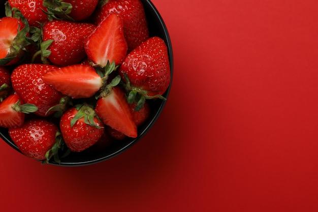 赤い表面に新鮮なイチゴのボウル