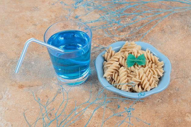 Чаша макаронных изделий фузилли и стакан синего коктейля на мраморном фоне. фото высокого качества