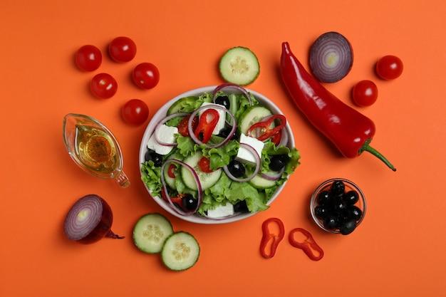 オレンジ色の表面にギリシャ風サラダと材料のボウル