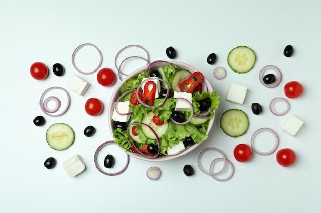 白い表面にギリシャ風サラダと材料のボウル、上面図