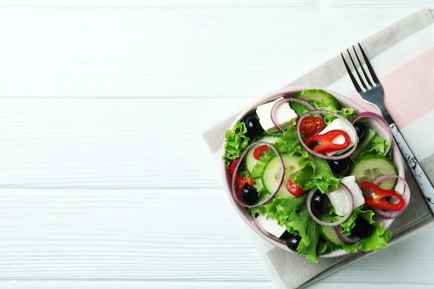 白い木製の背景にギリシャ風サラダのボウル