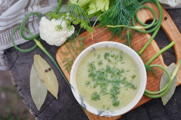 木製のテーブルの上の緑のクリームスープのボウル