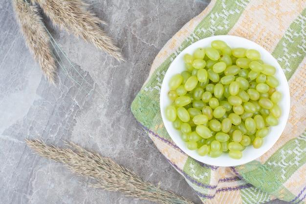 カラフルなテーブルクロスに緑のブドウのボウル。