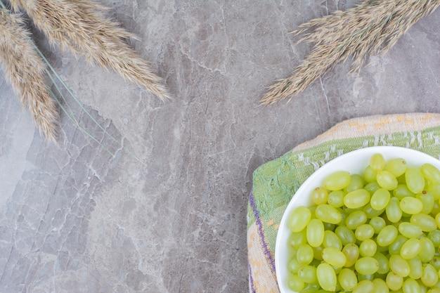 화려한 식탁보에 녹색 포도의 그릇입니다.