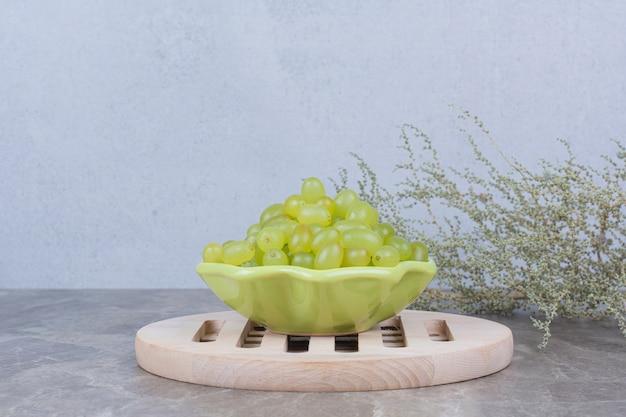 石のテーブルの上の緑のブドウのボウル。