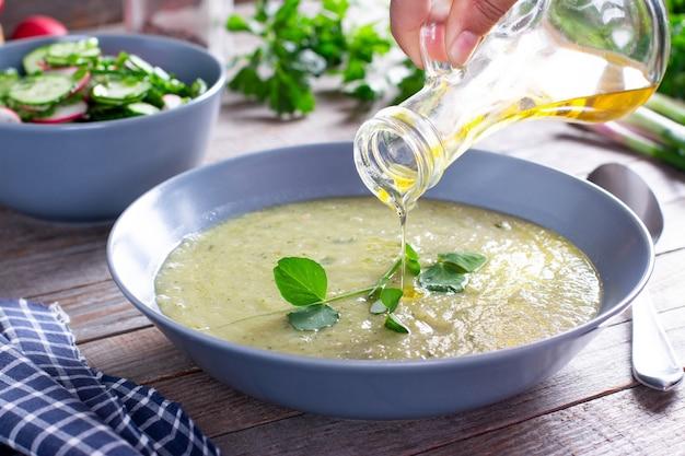 木製のテーブルにオリーブオイル、野菜スープとグリーンピースクリームスープのボウル