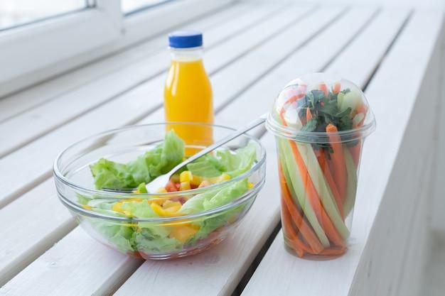 그린 샐러드 그릇, 생 야채와 오렌지 주스 한 병. 체중 감소, 다이어트 및 권리