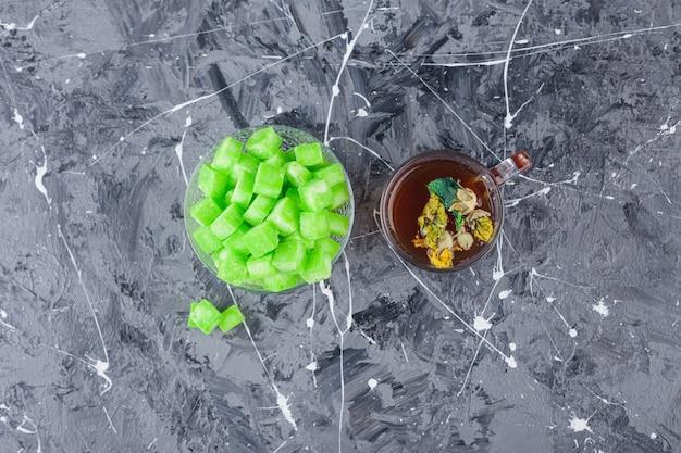 Чаша кубиков зеленого сахара и чашка чая на мраморной поверхности.