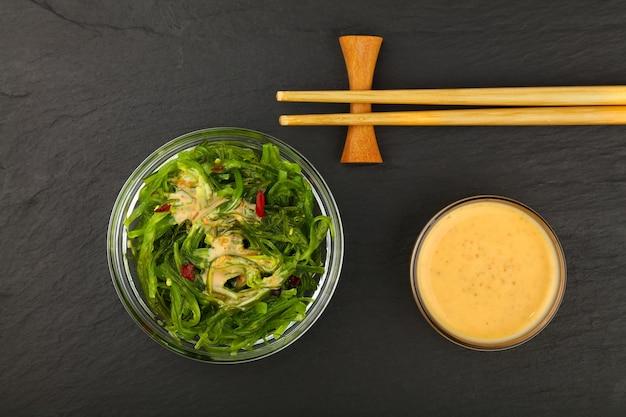 Чаша салата из зеленых водорослей вакаме с соусом сатай