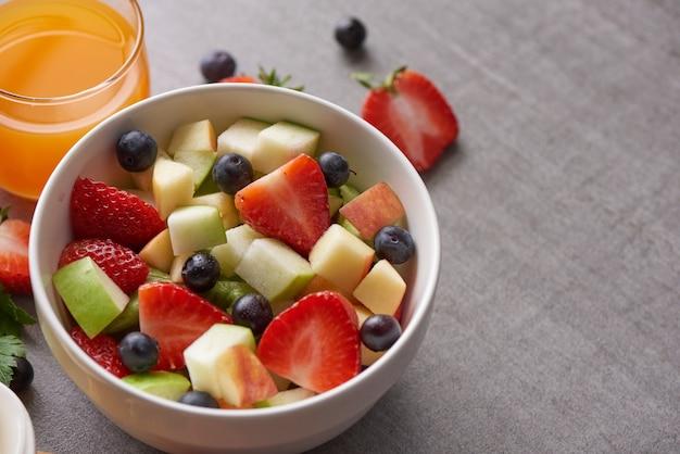 ヘルシーなフレッシュフルーツサラダのボウル。新鮮な果物と野菜のサラダ、健康的な朝食。