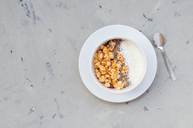 Чаша самодельной мюсли с йогуртом и семенами чиа на каменной поверхности, вид сверху. время завтрака