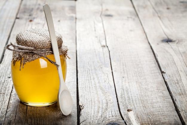 木製のテーブルの上に蜂蜜のボウル。健康的な生活と自然医学のシンボルです。芳香があり、おいしい。