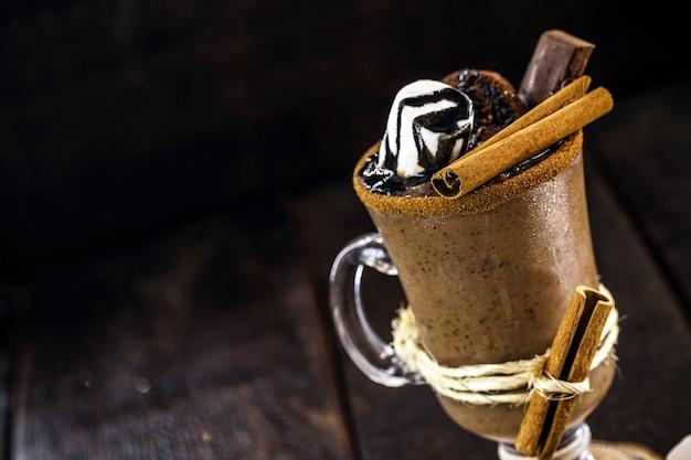 ホットシロップ、マシュマロ、ココア、砂糖を入れたホットチョコレートのボウル。黒の背景を持つ甘くて暑い冬の飲み物