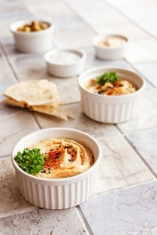 Чаша хумуса, традиционных еврейских, арабских, ближневосточных блюд из нута с глубиной и с лепешками из лаваша на фоне керамической плитки. крупным планом, выборочный фокус