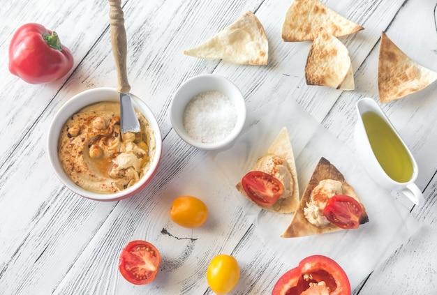 Чаша хумуса с чипсами и тортилья