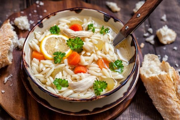 Чаша итальянского лимонного куриного супа орзо. деревенский стиль