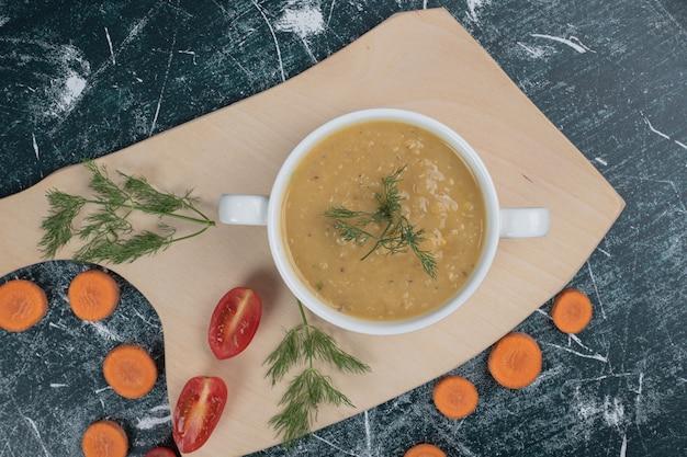 木の板ににんじんとトマトのスライスが入ったレンズ豆のスープのボウル。高品質の写真