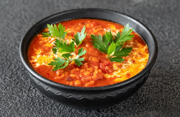 렌즈 콩 토마토와 코코넛 수프 그릇을 닫습니다.