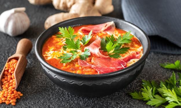 얇게 썬 프로슈토를 곁들인 렌즈 콩 토마토와 코코넛 수프 그릇