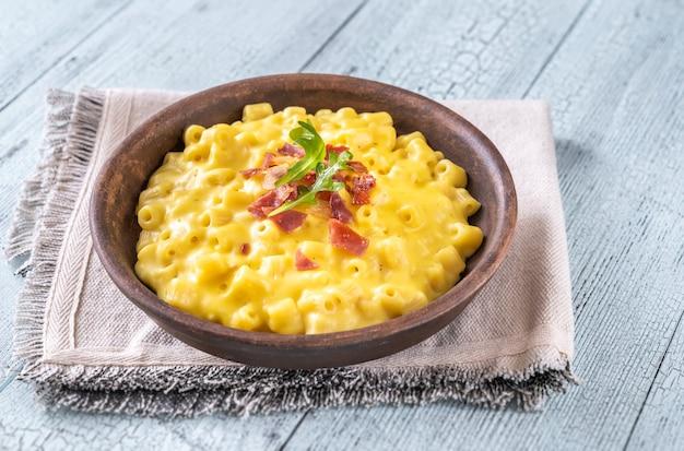 マカロニとチーズのボウルと揚げベーコンのスライス