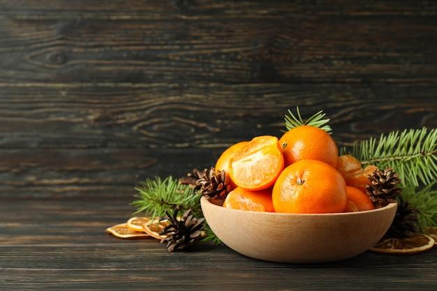 素朴な木製のテーブルにみかん、コーン、トウヒの枝のボウル